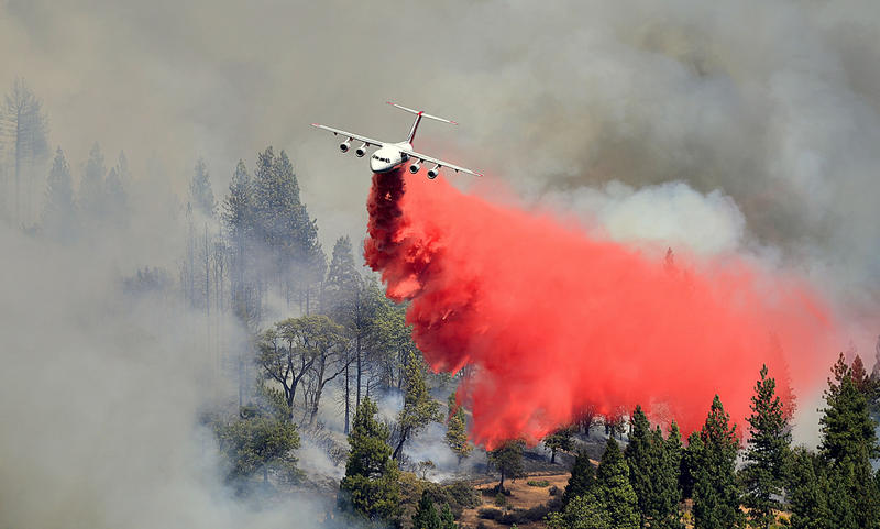 An air tanker from our featured member, Neptune Aviation, drops retardant on a fire.